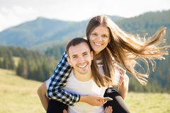 Happy couple in love walk on top of mountains. Young happy man holds girlfriend in arms royalty free stock photos