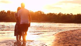 Couple in love on beach. Happy couple in love walk on water near beach and kiss each other during sunset in spring / summer stock video
