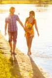 Happy couple in love walking on the beach. Summer vacations conc Royalty Free Stock Image