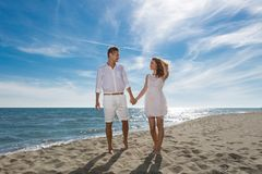 Happy couple in love walking on the beach Stock Image