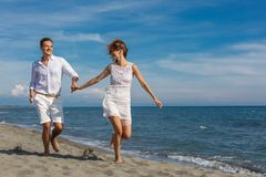 Happy couple in love walking on the beach Stock Photos