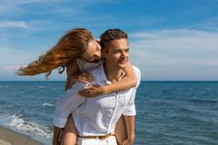 Happy couple in love walking on the beach Stock Photo