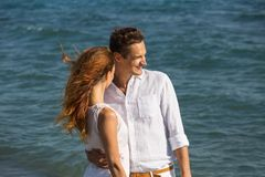 Happy couple in love walking on the beach Royalty Free Stock Images