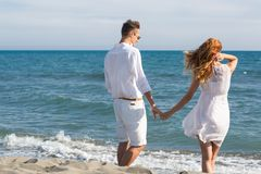 Happy couple in love walking on the beach Stock Photography