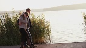 Happy couple in love, walks on a lake quay. Slowly stock video footage