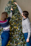 Happy couple of lovers decorating Christmas tree Stock Photography
