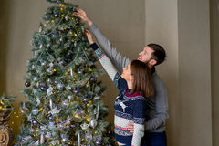 Happy couple of lovers decorating Christmas tree Royalty Free Stock Photos