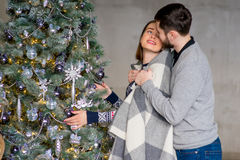 Happy couple of lovers decorating Christmas tree Royalty Free Stock Photography