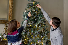 Happy couple of lovers decorating Christmas tree Royalty Free Stock Image