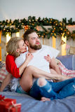 Happy couple of lovers hug sitting on the bed. Christmas tree and New Year at home. Young family together Royalty Free Stock Photography