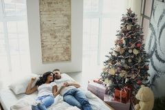 Happy couple of lovers lie on the bed. Christmas interior. Lovers together Stock Photos