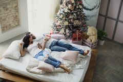 Happy couple of lovers lie on the bed. Christmas interior. Lovers together Stock Image