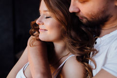 Happy couple of lovers in pajamas man embracing girl from behind. closed eyes. stock image