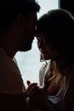 Happy couple of lovers in pajamas sit on the windowsill. Silhouette. Close up kiss. Royalty Free Stock Photo