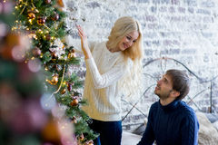 Happy couple of lovers in pullovers decorating Christmas tree Stock Images