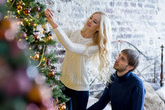 Happy couple of lovers in pullovers decorating Christmas tree Stock Photography