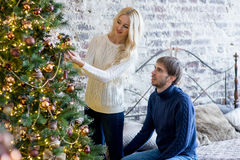 Happy couple of lovers in pullovers decorating Christmas tree Stock Image