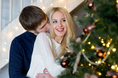 Happy couple of lovers in pullovers decorating Christmas tree Royalty Free Stock Photography