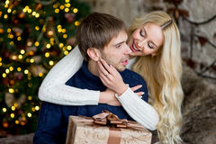 Happy couple of lovers in pullovers give each other gifts Stock Photo