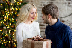 Happy couple of lovers in pullovers give each other gifts Royalty Free Stock Photography