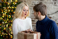 Happy couple of lovers in pullovers give each other gifts Royalty Free Stock Photos