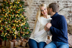 Happy couple of lovers in pullovers give each other gifts Royalty Free Stock Image