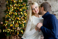 Happy couple of lovers in pullovers give each other gifts Royalty Free Stock Images