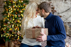 Happy couple of lovers in pullovers give each other gifts Stock Image