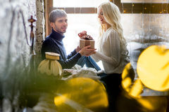 Happy couple of lovers in pullovers give each other gifts sitting Royalty Free Stock Photo