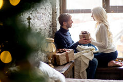 Happy couple of lovers in pullovers give each other gifts sitting Royalty Free Stock Images