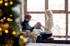 Happy couple of lovers in pullovers give each other gifts sitting Stock Image