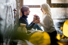 Happy couple of lovers in pullovers give each other gifts sitting Stock Images