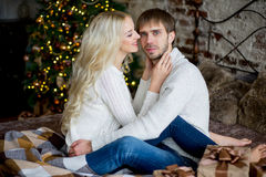 Happy couple of lovers in pullovers look each other sitting Stock Image
