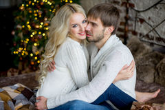 Happy couple of lovers in pullovers look each other sitting Stock Photo