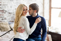 Happy couple of lovers in pullovers look each other sitting Royalty Free Stock Photo