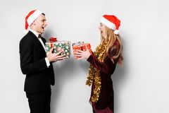 A happy couple of lovers in Santa Claus hats giving each other C stock photography