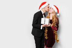 A happy couple of lovers, in Santa Claus hats, the guy kisses th royalty free stock image