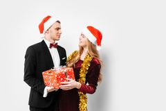 A happy couple of lovers, in Santa Claus hats, looking at each o stock image