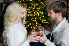 Happy couple of lovers in white pullovers give each other gifts Royalty Free Stock Image