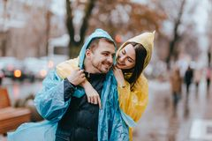 Happy couple loving guy and his girlfriend dressed in raincoats are hugging on the street in the rain stock photography