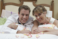 Happy Couple Lying In Bed Royalty Free Stock Photography