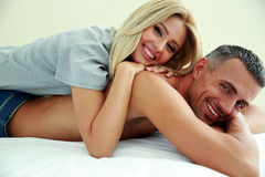 Happy couple lying on bed Royalty Free Stock Images