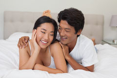 Happy couple lying on bed Stock Images