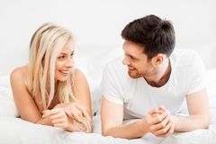 Happy couple lying in bed at home. Love, relationships and people concept - happy couple lying in bed at home royalty free stock photos
