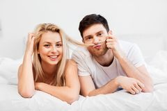Happy couple lying in bed at home. Love, relationships and people concept - happy couple lying in bed at home royalty free stock image