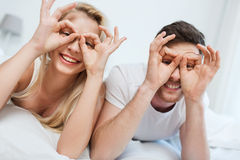 Happy couple lying in bed at home Royalty Free Stock Image
