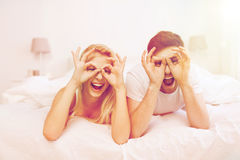 Happy couple lying in bed at home Royalty Free Stock Photography