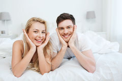 Happy couple lying in bed at home Royalty Free Stock Images