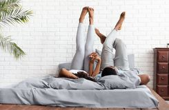 Happy couple lying on bed at home raising legs up royalty free stock photos