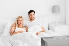 Happy couple lying in bed at home and watching tv. People, leisure and rest concept - happy couple lying in bed at home and watching tv royalty free stock photo
